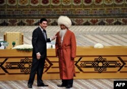 Түркіменстан президенті Гурбангулы Бердімұхаммедов (сол жақта) түркімен ақсақалымен кездесіп тұр. Түркіменстан, 10 қыркүйек 2015 жыл.