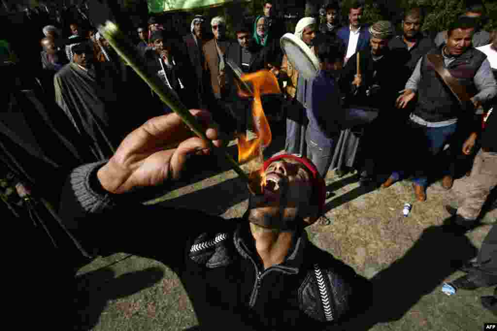 An Iraqi Muslim eats fire during a Sufi ritual, attended by Sunni and Shi'a, in the city of Hilla, south of Baghdad, on January 15. (AFP/Haidar Hamdani)