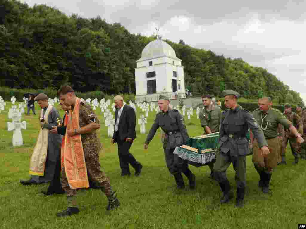 "Activists of the Pamiat, or Memory Searching Organization, for victims of World War II, carry the coffin with the remains of Ukrainian, German, and Soviet soldiers of the ""Galician"" SS Division during a reburial ceremony near Chervone, some 70 kilometers from the western Ukrainian city of Lviv, on July 24. Photo by Yuriy Dyachyshyn for AFP"