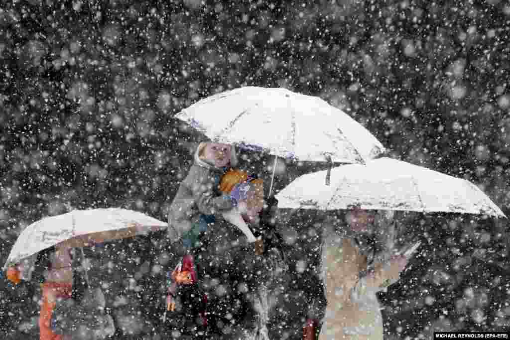 Маленька дівчинка сидить на плечах у тата, 21 березня, під час сніжної завірюхи в центрі Вашингтона. (epa-EFE/Michael Reynolds)