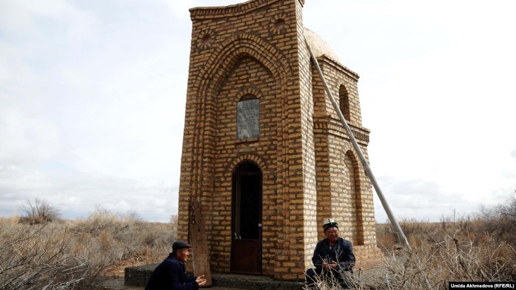 Рақымбай ата (оң жақта) мен Досболат Шугураев Көкен Қойбағарұлының мазары басында құран бағыштап отыр.
