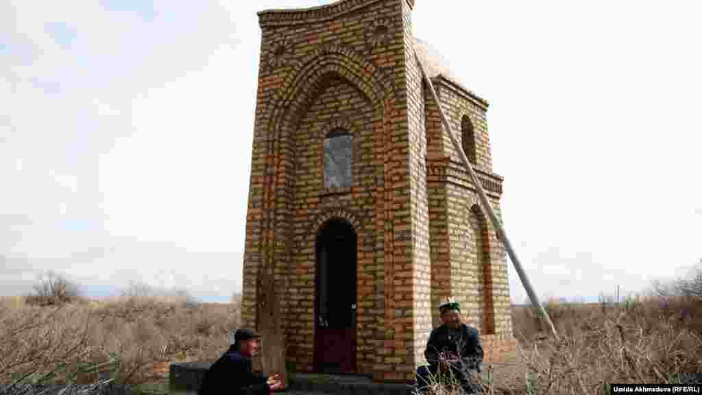 Ракымбай-ата (справа) и Досполат Шугураев читают молитву на могиле Кокена Койбагарулы.