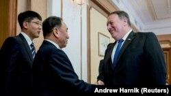 АҚШ Мемлекеттік хатшысы Майк Помпео (оң жақта) Солтүстік Корея ресми өкілімен қол алысып тұр. Пхеньян, 6 шілде 2018 жыл.