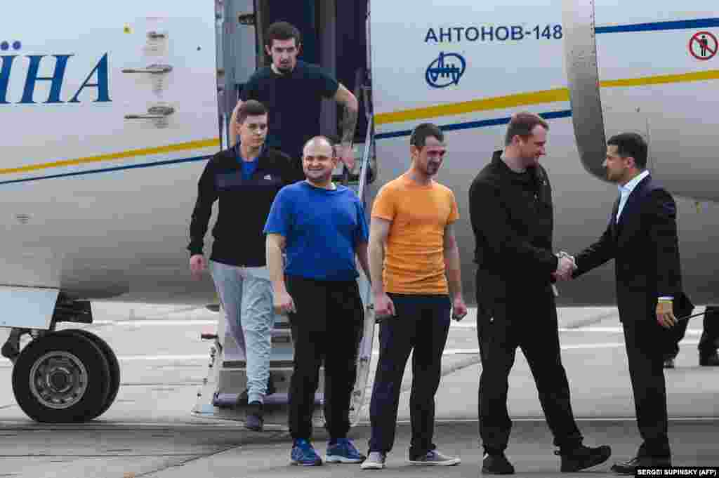 Ukraine's President Volodymyr Zelenskiy welcomes former prisoners as they disembark from a plane on September 7 at Boryspil international airport in Kyiv after a long-awaited exchange of prisoners between Moscow and Kyiv.