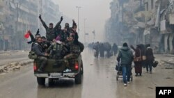 Syrian pro-regime fighters gesture as they drive past residents fleeing violence in Aleppo.