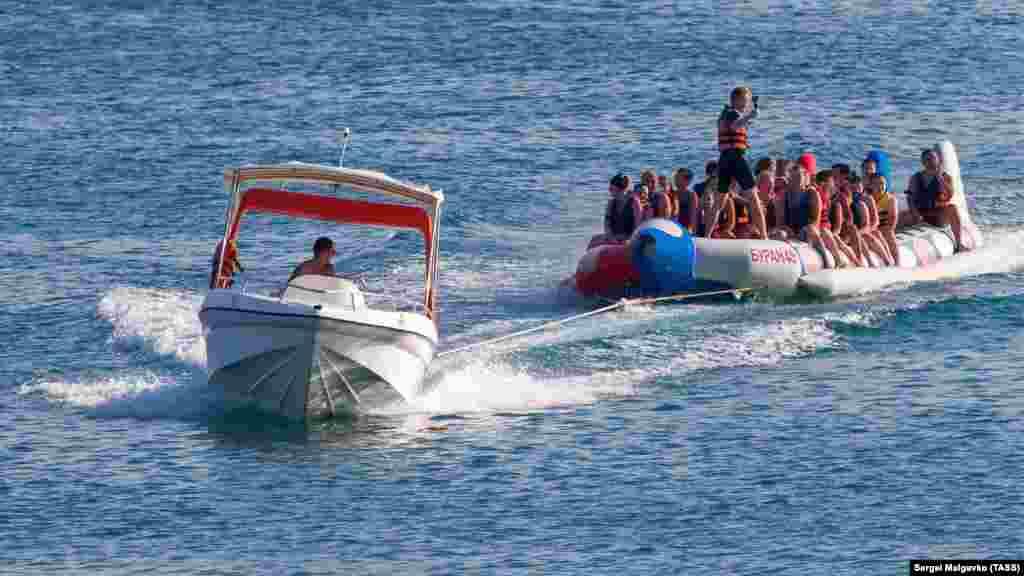 Отдыхающие в Судаке катаются на надувной лодке по Черному морю