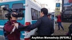 Азаттықтың түсірілім тобына кедергі жасап тұрған адам. Алматы, 22 наурыз 2019 жыл.