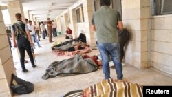Люди осматривают тела убитых боевиками группировки ИГ в провинции Хасака в Ираке. Рас аль-Айн, 29 мая 2014 года.