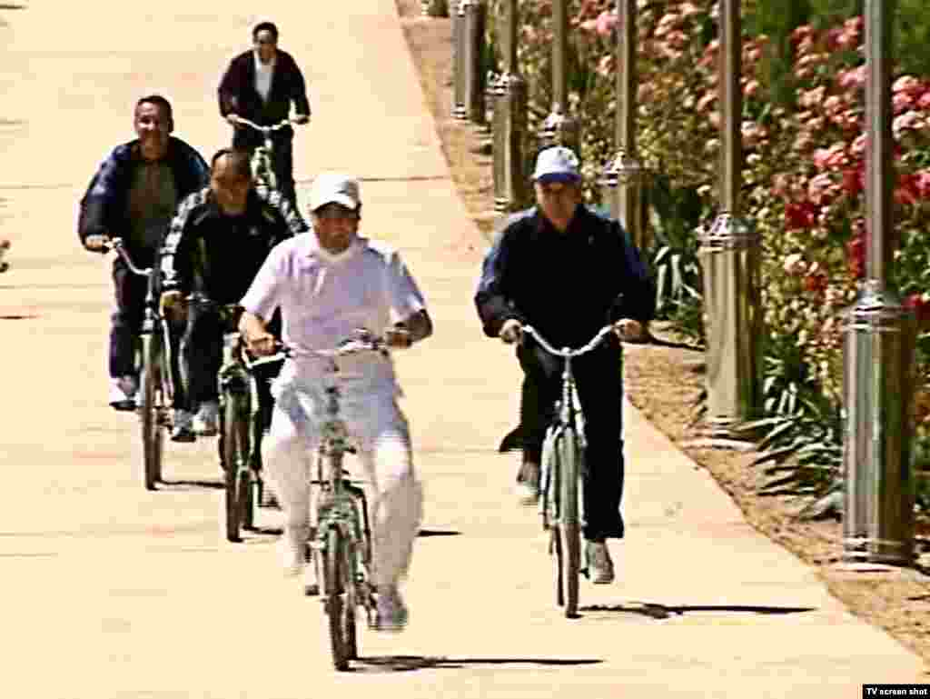 Even in leisure time, white is the color of choice for the Turkmen president, shown here bicycling with black-clad minders. Berdymukhammedov is frequently seen wearing white sweaters and fleece jackets during casual public appearances.