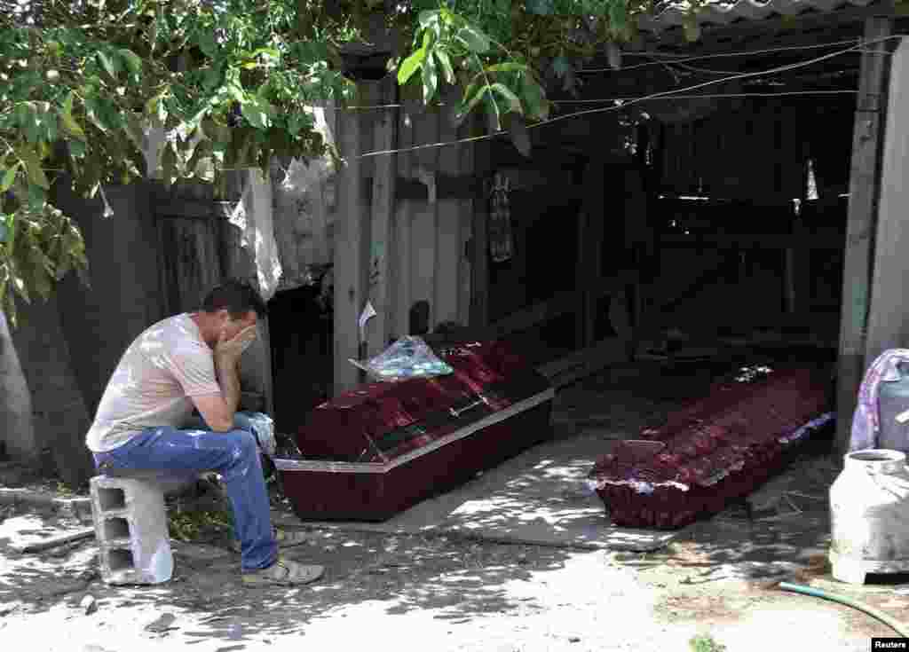 A man whose mother was killed by shelling, according to locals, reacts while sitting near her coffin outside her damaged house before her funeral in Donetsk on July 7. (Reuters/Igor Tkachenko)