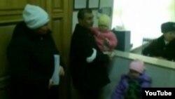 Исраил Азнабкиев, житель села Атамекен Мунайлинского района (в центре) со своей женой и детьми на акции протеста в акимате Мангистауской области. Кадр видеозаписи на сайте «Ютуб». Актау, 23 января 2012 года.