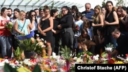 Mourners pay their respects at the site where an 18-year-old German-Iranian student run amok and killed nine people.