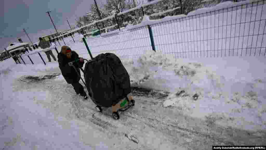 Nikolayevna at work, pushing a load of fruits and vegetables through slushy snow toward separatist-held territory. Such fresh items are significantly more expensive in the separatist region.