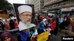 Supporters of Tahir-ul Qadri,hold his portrait during a protest in Karachi on June 19, 2014.