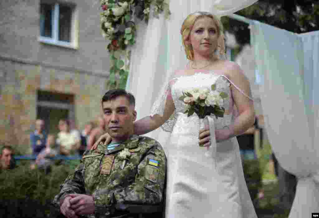 Ukrainian serviceman Sergiy Yushchenko (left) and his bride, Kateryna, at their wedding in the military hospital in Lviv. Sergiy was wounded and paralyzed during fighting with pro-Russia militants. (epa/Markiian Lyseiko)