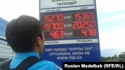 Мужчина смотрит на информационное табло с курсами валют рядом с обменным пунктом. Алматы, 23 июля 2013 года.