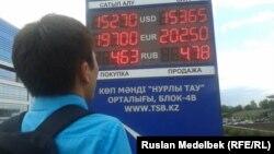 Молодой человек смотрит на табло обменного пунка. Алматы, 23 июля 2013 года.