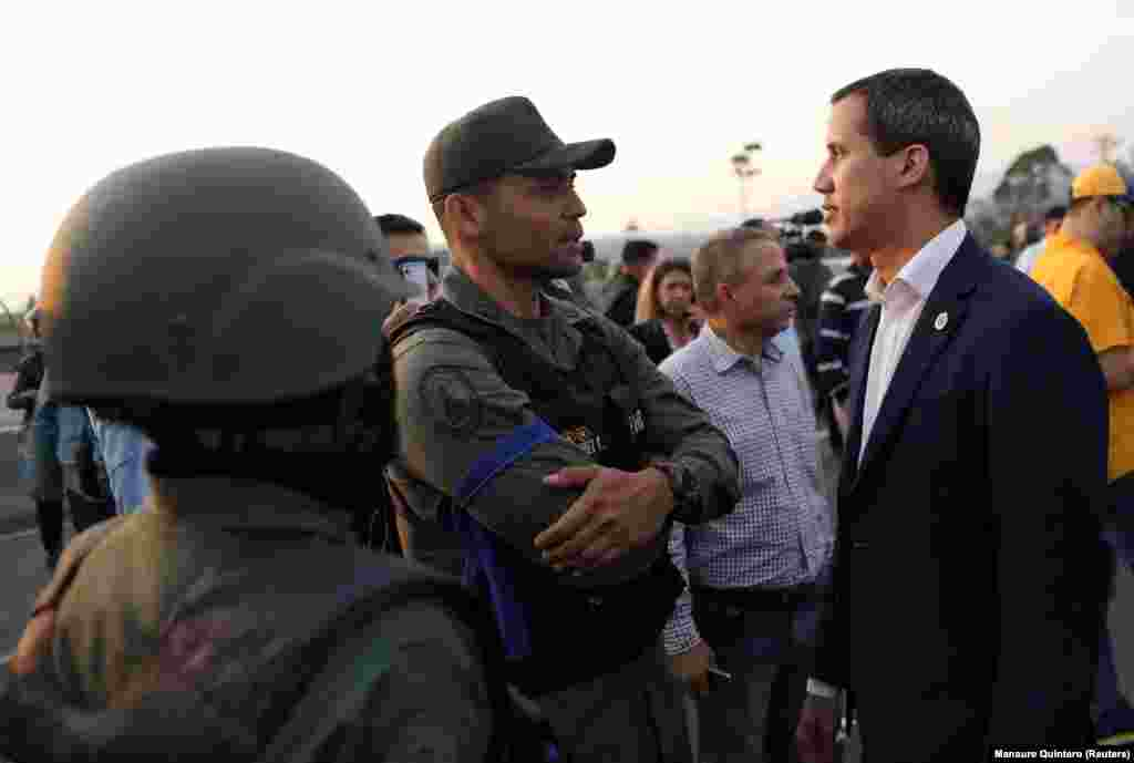 Venezuelan opposition leader Juan Guaido, whose claim to the presidency is backed by the United States and other countries, speaks with a man in uniform near the air base shortly after sunrise in the Venezuelan capital.