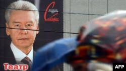 Muscovites walk past an election poster hanging on the Theater of Satire of incumbent Mayor Sergei Sobyanin ahead of the September 8 voting.