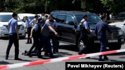 Полиция шабуылдан соң ер адамды тұтқындап әкетіп барпады. Алматы, 18 шілде 2018 жыл.