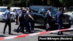 Алматы орталығында шабуылға ұшыраған полицейді көтеріп бара жатқан адамдар. 18 шілде 2016 жыл.