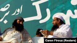 FILE: Hizb ul-Mujahideen chief Syed Salahuddin (L), speaking with Hafiz Muhammad Saeed, chief of the Jamaat-ud-Dawa during a protest in Islamabad.