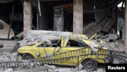A damaged car lies among rubble after an explosion in the Al-Zahraa neighborhood of Homs in May 2017.