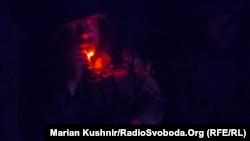 Михаил курит в полной темноте блиндажа во время наблюдения на передовых позициях