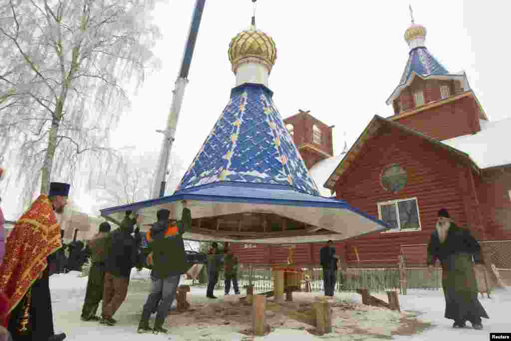 People lift a dome on an Orthodox church in the Belarusian town of Smilovichi, east of Minsk. (Reuters/Vasily Fedosenko)