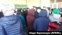 Гражданские и полиция в защитных масках у склада с продуктами.