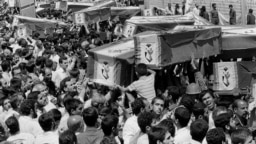 Mourners carry coffins through the streets of Tehran during a mass funeral for the victims of Iran Air Flight 655, which was shot down by the USS Vincennes in the Persian Gulf on July 7, 1988.