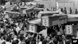 Mourners carry coffins through the streets of Tehran during a mass funeral for the victims aboard Iran Air Flight 655, which was shot down by the USS Vincennes in the Persian Gulf, July 7, 1988. Iran claims the shooting down of a passenger plane was act o