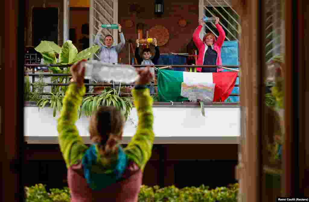 With Italians unable to leave their homes due to the coronavirus, a personal trainer leads an exercise class for her neighbors from her balcony in Rome. (Reuters/Remo Casilli)