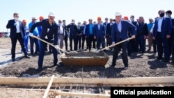 A hopeful sign of cooperation in Central Asia: Uzbek Prime Minister Abdullo Aripov (left) and his Kazakh counterpart, Askar Mamin, pose for photographs as repair work begins following the recent Sardob Reservoir disaster.