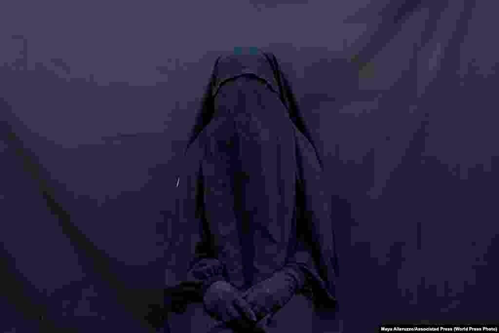 Езидка Лейла Талу позириует для портера в своем доме, Ирак (9 сентября 2019). Эту закрывающую лицо вуаль и абайю она проносила два с половиной года, будучи рабыней у боевиков «ИГ». Второе место в категории «Проблемы современности, фоторепортаж», автор –Майя Аллеруццо
