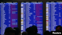 Passengers crowd in front of a flight board at the departure hall of Moscow's Domodedovo Airport on December 28.