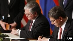 Switzerland -- Armenia's Foreign Minister Eduard Nalbandian (L) and his Turkish counterpart Ahmet Davutoglu sign documents during the signing ceremony of Turkey and Armenia peace deal in Zurich, 10Oct2009