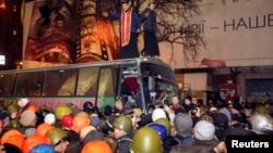 Автобус с солдатами внутренних войск покидает место демонстрации протеста. Киев, 21 февраля 2014 года.