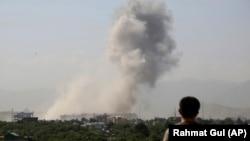 Житель Кабула наблюдает за взрывом в центре города, 1 июля 2019 г.