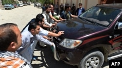 Afghan security personnel and police push the vehicle from which a German female aid worker was kidnapped by armed gunmen at the entrance to the office of German development agency GIZ in Kabul on August 17.