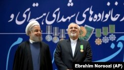 "Iranian President Hassan Rohani, left, and his Foreign Minister Mohammad Javad Zarif pose for a photograph after Zarif was awarded a ""Medal of Merit"" in a ceremony in Tehran, February 8, 2016"