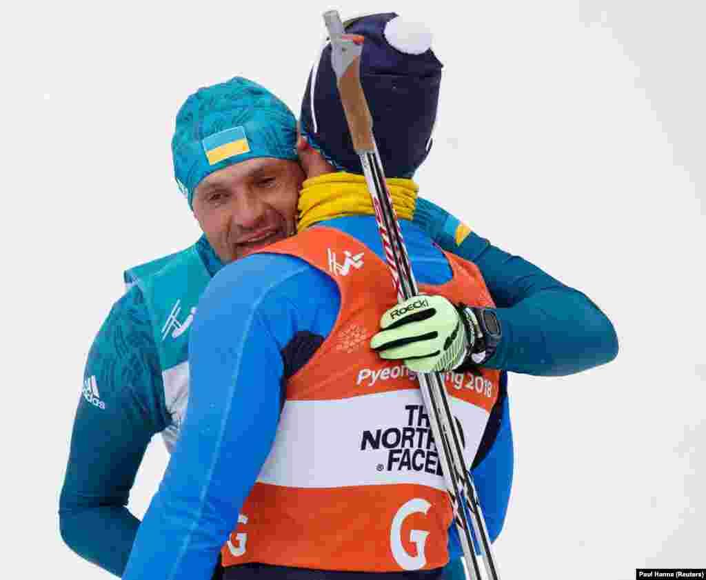 Виталий Лукьяненко из Украины и его гайд Иван Марчишак поздравляют друг друга после победы в 15-километровом забеге биатлонистов с ограниченными возможностями в Центре биатлона «Альпенсия»