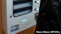 Студент колледжа опускает монету в аппарат по продаже презервативов. Темиртау, 29 января 2015 года.