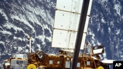 The STS-48 onboard photo of the Upper Atmosphere Research Satellite (UARS) in the grasp of the RMS (Remote Manipulator System) during deployment in September 1991.