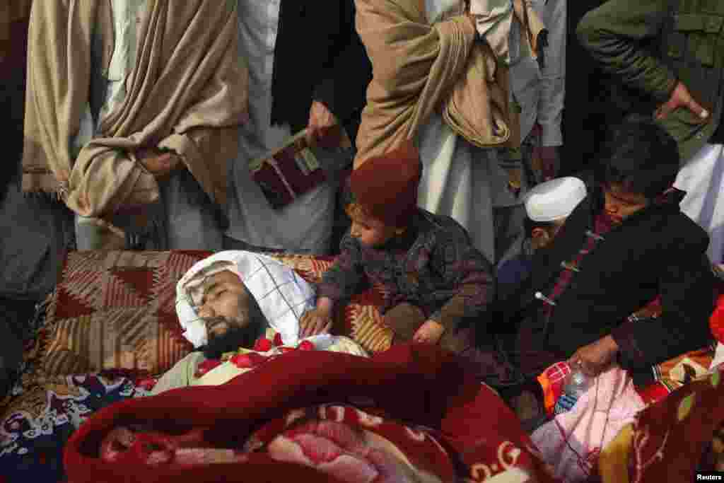 Children sit beside one of 14 victims whom tribesmen said were killed by security forces in the northwestern Pakistani city of Peshawar. Protesters said men in uniforms raided their homes in the Sipah Alam Goodar area overnight and shot the villagers dead. Villagers laid the bullet-riddled bodies of their relatives in front of the governor's house in Peshawar. (Reuters/Fayaz Aziz)