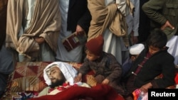 Children sit beside the body of one of the victims during a protest in front of the government offices in Peshawar.