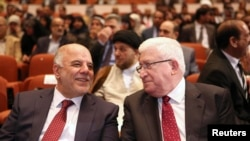 Iraq's new Prime Minister Haider al-Abadi (left) and Iraqi President Fuad Massum speak during the session to approve the new government in Baghdad on September 8.