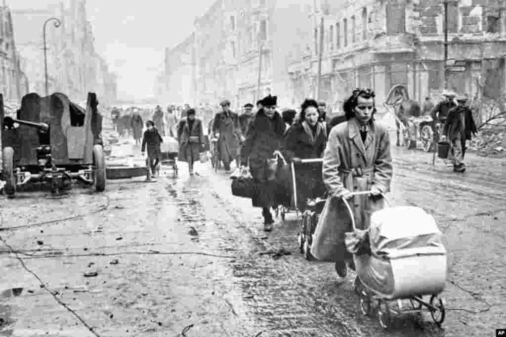 "Civilians walking along a decimated Berlin street.   Thousands of German women were raped by Soviet soldiers, forcing many female Berliners to hide in the evening during ""hunting hours"" and emerge only in the early morning when Soviet troops were asleep."