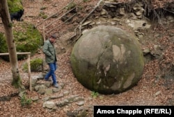 A man who runs a small cafe next to this stone sphere discovered in 2016 in a forest near the Bosnian town of Zavidovici.