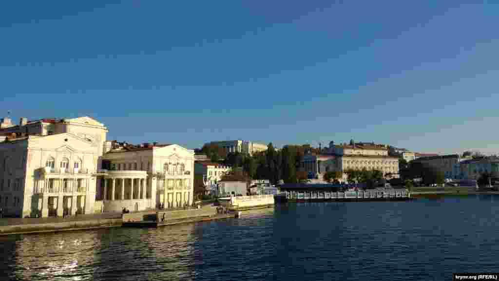 Слева открывается обзор на Приморский бульвар, в частности, на Дворец детства и юности, театр имени Луначарского, гостиницу «Севастополь»